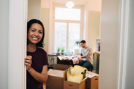 Portrait of smiling woman leaning on doorway at new home - MASF00167