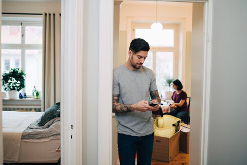 Mid adult man using mobile phone while leaning on doorway at new home - MASF00170