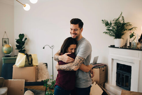 Smiling man embracing woman while standing in living room during relocation - MASF00182
