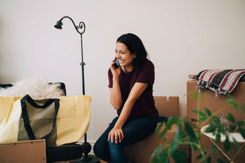 Smiling woman talking on mobile phone while sitting on box against wall - MASF00191
