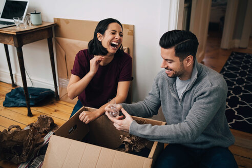 Laughing couple unpacking cardboard box while sitting on floor at home - MASF00194