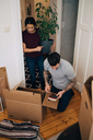 Woman holding potted plant while man reading book during unpacking boxes at house - MASF00197