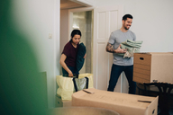 Couple unpacking boxes while standing in living room - MASF00200