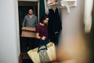 Couple carrying bag and box while moving in new house - MASF00203