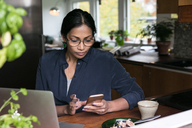 Businesswoman using mobile phone with laptop on table in home office - MASF00227