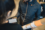 Man holding package while looking at customer's signature on mobile phone - MASF00230
