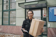 Portrait of smiling worker carrying box and holding phone while standing against building in city - MASF00233