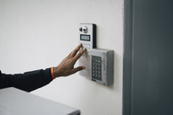 Cropped image of delivery man ringing intercom on wall - MASF00239