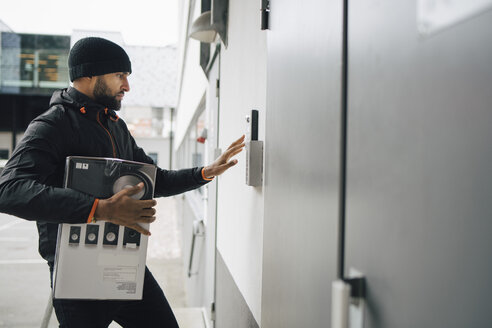 Male worker with box ringing intercom during delivery - MASF00242