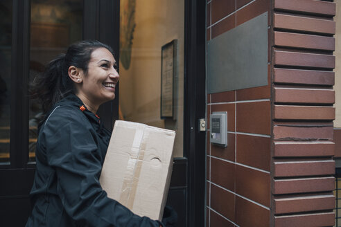 Smiling female messenger looking away while carrying box by closed door - MASF00254