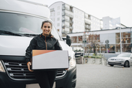 Portrait of smiling female worker carrying box while standing against delivery van in city - MASF00269