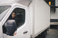 Smiling female worker driving white delivery van in city - MASF00284