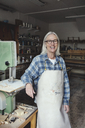 Portrait of smiling senior owner standing by machinery at workshop - MASF00287