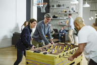 Business people playing foosball in office - CAVF34471