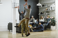 Businessmen playing basketball while colleagues sitting in background at office - CAVF34474