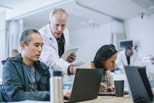 Male doctor discussing with coworkers over laptop computer in medical room - CAVF34504