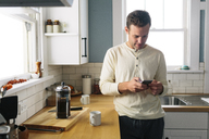 Man using smart phone while leaning by kitchen counter at home - CAVF34573