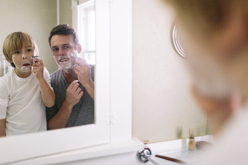 Father and son shaving while reflecting in mirror - CAVF34621
