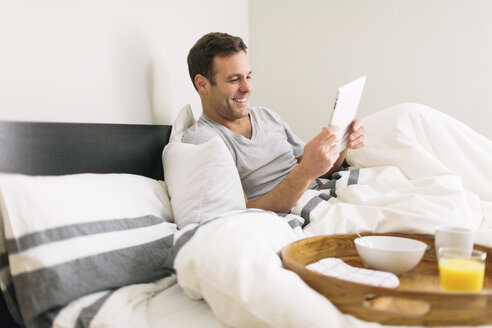 Man using tablet computer while sitting on bed at home - CAVF34636