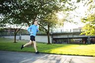 Full length of man jogging on footpath at park - CAVF34669