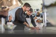 Chefs preparing food in restaurant kitchen - CAVF34693