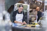 Female chef garnishing food while coworker working in background at restaurant kitchen - CAVF34702
