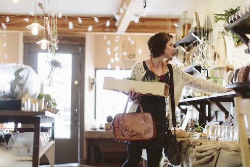 Customer examining plants in garden center - CAVF34762
