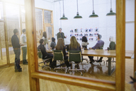 Business people in meeting at board room seen through glass - CAVF34786