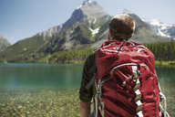 Male hiker carrying backpack at Glacier National Park - CAVF34912