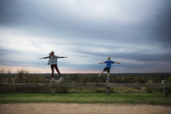 Teenage girl and boy standing on one leg on wooden fence against sky - CAVF35077