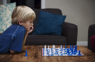 Blonde boy playing chess at table - CAVF35083