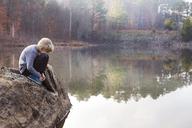 Boy sitting on rock by lake - CAVF35107