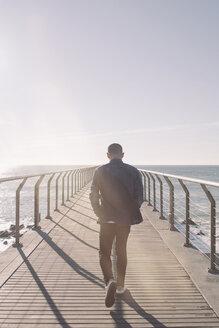 Back view of man walking on boardwalk at backlight - SKCF00397