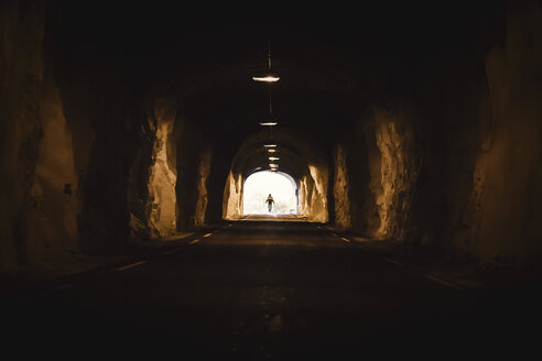 Norway, Lofoten Islands, Maervoll, silhouette of man at the end of a tunnel - WVF00966