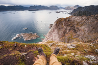 Norway, Lofoten Islands, Henningsvaer, hiker sitting on viewing point - WVF00990
