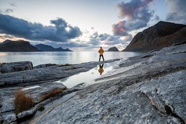 Norway, Lofoten Islands, Haukland Beach, hiker standing on rock - WVF01036
