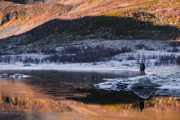Norway, Lofoten Islands, man standing at water's edge in winter landscape - WVF01054