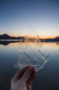 Norway, Lofoten Islands, man's hand holding thin ice - WVF01075