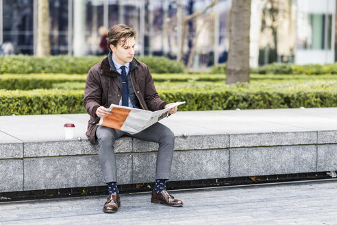 Businessman reading newspaper outdoors - WPEF00172
