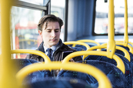 UK, London, portrait of businessman sitting in bus looking at cell phone - WPEF00175