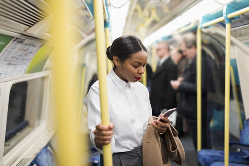 UK, London, businesswoman in underground train looking at cell phone - MAUF01365