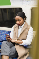 UK, London, portrait of businesswoman in underground train looking at cell phone - MAUF01368