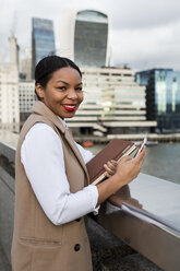 UK, London, portrait of smiling businesswoman standing on bridge with cell phone - MAUF01380