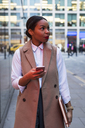 Smiling businesswoman with cell phone - MAUF01389