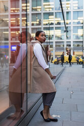 Smiling businesswoman leaning against glass pane looking up - MAUF01392