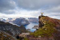 Norway, Lofoten Islands, Reine, Man with raised arms on Reinebringen - WVF01092