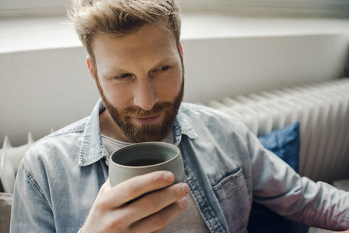 Man relaxing at home, drinking coffee - KNSF03730