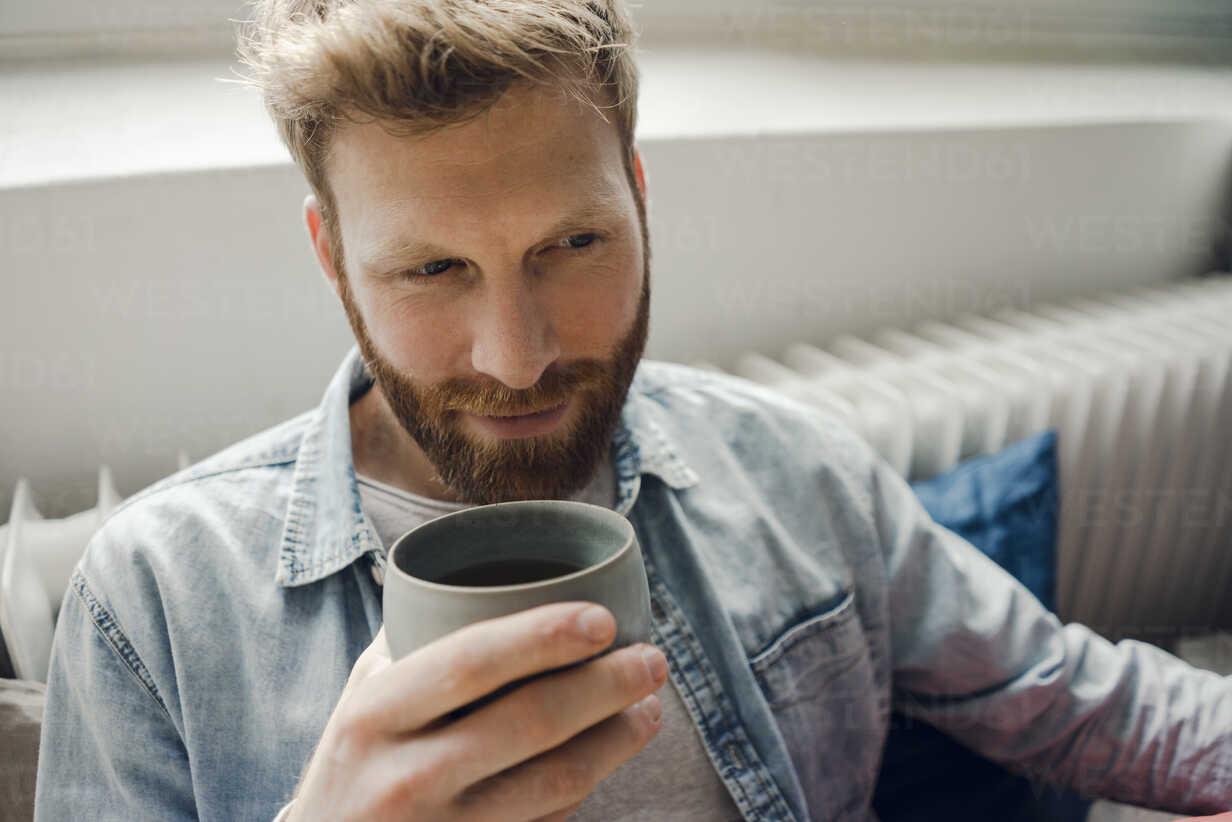 Man relaxing at home, drinking coffee - KNSF03730 - Kniel Synnatzschke/Westend61