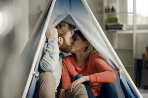 Happy couple at home camping ina tent in the livingroom - KNSF03736