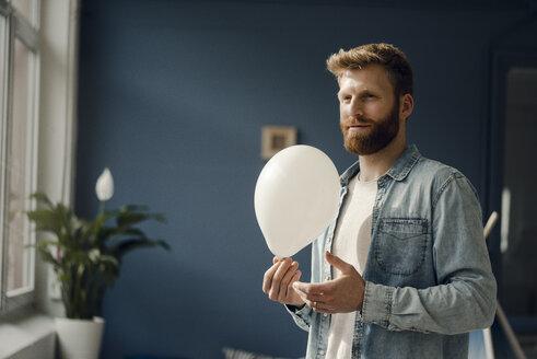 Man holding a balloon, smiling - KNSF03739